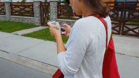 Vrouwelijke studentenoortelefoons die in smartphone app, het lopen straat, het levensgevaar kijken stock videobeelden