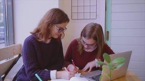 Vrouwelijke studentenstudies in koffie twee meisjesvrienden die samen leren stock videobeelden
