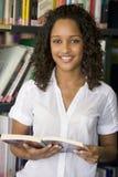 Vrouwelijke studentlezing in een bibliotheek Stock Foto's