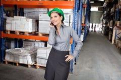 Vrouwelijke Supervisor die Celtelefoon met behulp van bij Pakhuis Stock Foto's