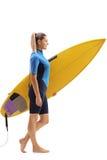 Vrouwelijke surfer die met surfplank loopt stock afbeelding