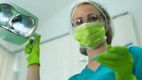 Vrouwelijke tandarts die beschermingsglazen, aandacht, de professionele diensten dragen stock footage