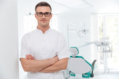 Vrouwelijke tandarts die zich met zijn gekruiste handen bevinden Stock Foto's