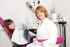 Vrouwelijke tandarts met röntgenstraal en meisje Royalty-vrije Stock Foto's