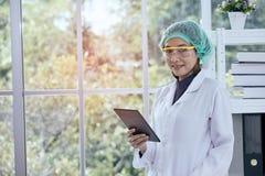 Vrouwelijke taplet van de wetenschapperholding voor controlegegevens stock foto