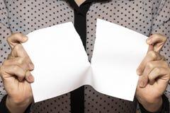 Vrouwelijke tearing handen een blad van document, close-up stock fotografie