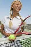 Vrouwelijke Tennisspeler bij netto op tennisbaan stock afbeeldingen