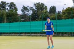 Vrouwelijke tennisspeler die een tennisbal op haar racket houden Stock Afbeelding