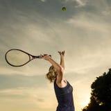 Vrouwelijke tennisspeler ongeveer om de bal te dienen Stock Foto's