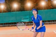 Vrouwelijke tennisspeler tijdens het spel op de achtergrond w van het kleihof Stock Fotografie