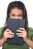 Vrouwelijke tiener die hal haar gezicht achter boek verbergt Royalty-vrije Stock Foto