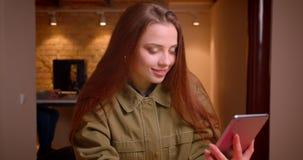Vrouwelijke tienerblogger zet app op tablet aan en toont het zijn groen chromascherm die blij in bureau zijn stock videobeelden