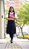 Vrouwelijke Tienerstudent Walking On Sidewalk stock foto's