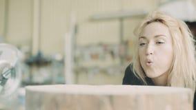 Vrouwelijke Timmerman Blowing Sawdust stock footage