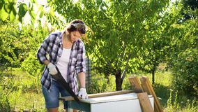 Vrouwelijke timmerman die camera en knipsel houten plank bekijken met handzaag stock footage