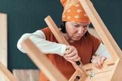 Vrouwelijke timmerman die houten stoelzetel in workshop herstellen stock afbeeldingen