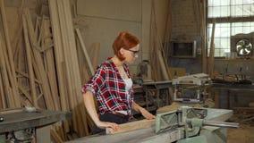 Vrouwelijke timmerman die machtshulpmiddelen met behulp van op haar workshop stock footage