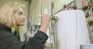 Vrouwelijke Timmerman Painting Tree Stump in Workshop stock video
