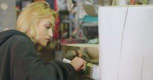 Vrouwelijke Timmerman Painting Tree Stump in Workshop stock footage