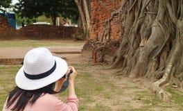 Vrouwelijke Toerist die Beelden van het Hoofd nemen van het Beeld van Boedha dat in Bodhi-Boomwortels wordt opgesloten, Wat Mahat royalty-vrije stock foto's