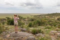 Vrouwelijke toerist die door verrekijkers op Afrikaanse safari in het nationale park van Serengeti kijken Tanzania, Afrika royalty-vrije stock fotografie