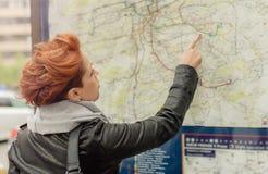 Vrouwelijke toerist die openbare straatkaart bekijken stock foto
