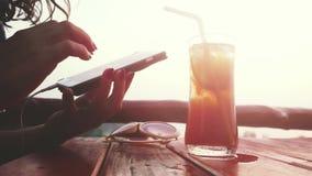 Vrouwelijke toerist die van rust op strandkoffie genieten tijdens zonsondergang die via mobiel babbelen 3840x2160 stock videobeelden