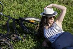 Vrouwelijke toerist met fiets die op gras liggen Royalty-vrije Stock Foto