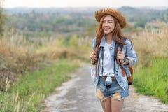 Vrouwelijke toerist met rugzak en camera in platteland stock foto's