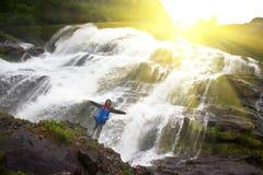 Vrouwelijke toerist onder waterdalingen van bergen van Noorwegen Stock Foto