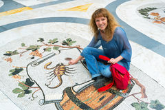 Vrouwelijke toerist op het Dierenriemteken Schorpioen in Galleria Umberto I Royalty-vrije Stock Foto's
