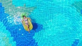 Vrouwelijke toeristenrust op opblaasbare rubberring in een pool De vakantieconcept van de zomer stock videobeelden