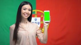 Vrouwelijke tonende telefoon met het groene scherm, Duitse vlag op achtergrond, reis app stock videobeelden