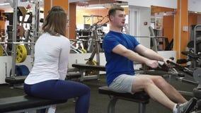 Vrouwelijke trainer die newbie tonen hoe te Achter Hoogste Lagere training op barmachine in gymnastiek uit te voeren stock video