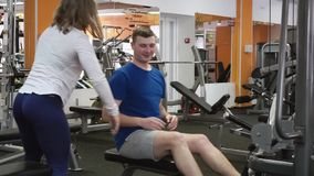 Vrouwelijke trainer die newbie weightloss Achter Hoogste Lagere trainingoefening op barmachine tonen in gymnastiek stock video