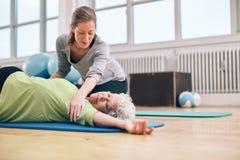 Vrouwelijke trainer die oudere vrouw in zich het uitrekken helpen stock afbeeldingen