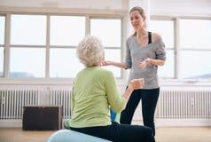 Vrouwelijke trainer die vooruitgang bespreken met bejaarde Stock Foto