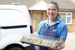Vrouwelijke Traiteur die Tray Of Sandwiches To House leveren royalty-vrije stock foto's
