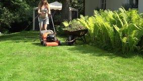 Vrouwelijke tuinman in borrels en het grasmaaimachine van het bustehouder duwende gazon dichtbij varen 4K stock videobeelden
