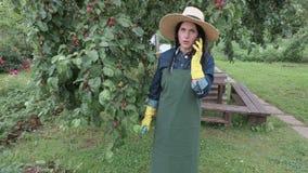 Vrouwelijke tuinman die op telefoon dichtbij appelboom spreken stock videobeelden