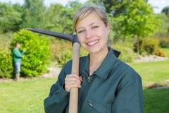 Vrouwelijke tuinman het glimlachen holdingspikhouweel royalty-vrije stock afbeelding
