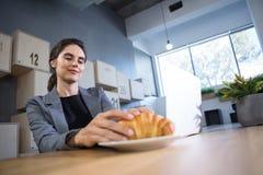 Vrouwelijke uitvoerend hebbend croissant bij lijst stock fotografie