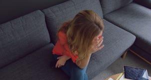 Vrouwelijke uitvoerende zitting op de bank in een modern bureau 4k stock videobeelden