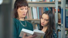 Vrouwelijke Universitaire Student Working In Library met Privé-leraar stock videobeelden