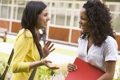 Vrouwelijke universiteitsvrienden die op campus spreken Stock Foto