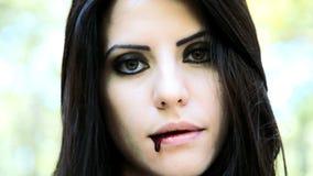 Vrouwelijke vampier die met bloed in mond glimlachen