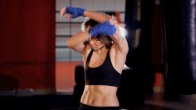 Vrouwelijke vechter die in boksersgymnastiek opwarmen stock footage