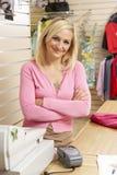 Vrouwelijke verkoopmedewerker in kledingsopslag royalty-vrije stock foto's