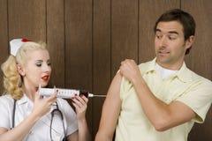 Vrouwelijke verpleegster die de mens geeft die met reuzespuit is ontsproten. Royalty-vrije Stock Fotografie