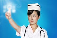 Vrouwelijke verpleegster die het futuristische aanrakingsscherm over blauwe achtergrond met behulp van Royalty-vrije Stock Afbeelding